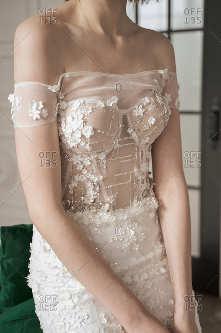 Magnificent pensive young bride in white lace dress looking away and pondering