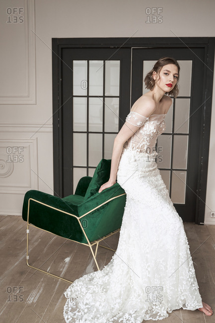 Barefooted slender bride in elegant white dress looking at camera while sitting on backrest of green armchair against black doors in spacious apartment