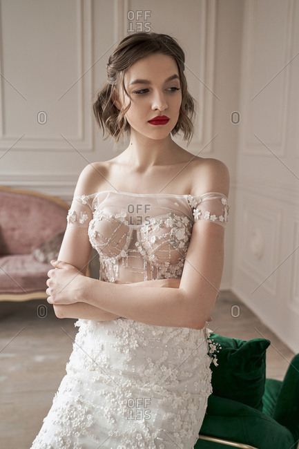 Melancholic woman in elegant white wedding dress looking away and thinking while sitting on backrest of green armchair in spacious apartment