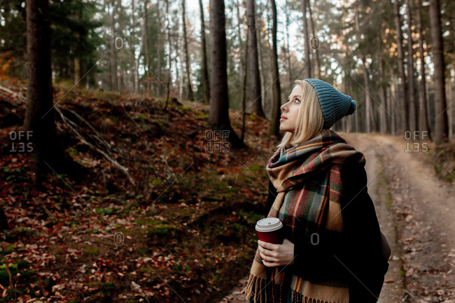 Beautiful blond girl in blue hat with a cup of coffee in a forest