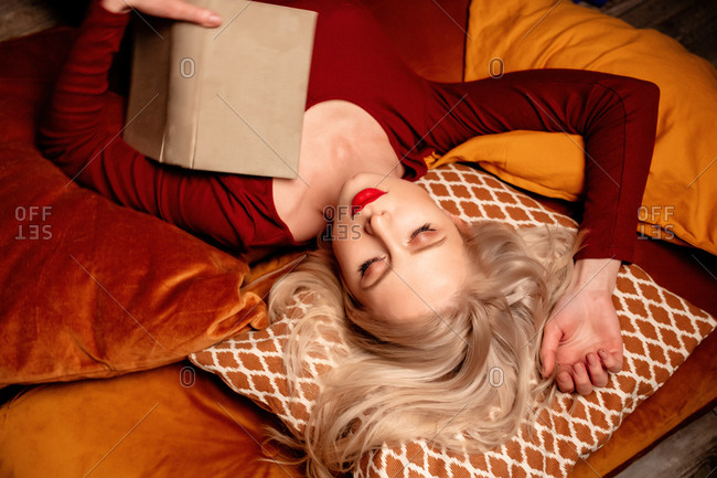 Young girl lies on a pillow with a book