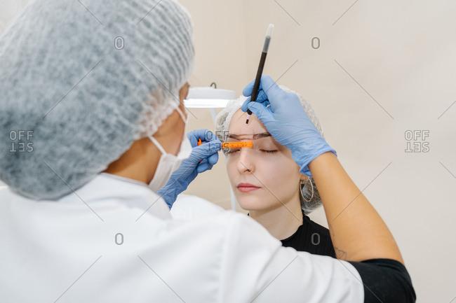Esthetician performs a corrector treatment of eyebrows on a young woman