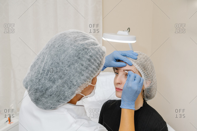 Beautician prepares a young woman before a beauty treatment in a beauty center