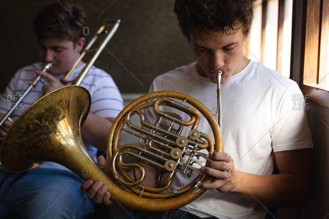 Front view of two Caucasian teenage male musicians rehearsing, one playing the French horn and one playing the trombone. High school education concept.