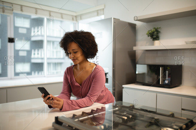 Front view of a mixed race woman relaxing at home, standing in the kitchen leaning on the worktop, using a smartphone and smiling