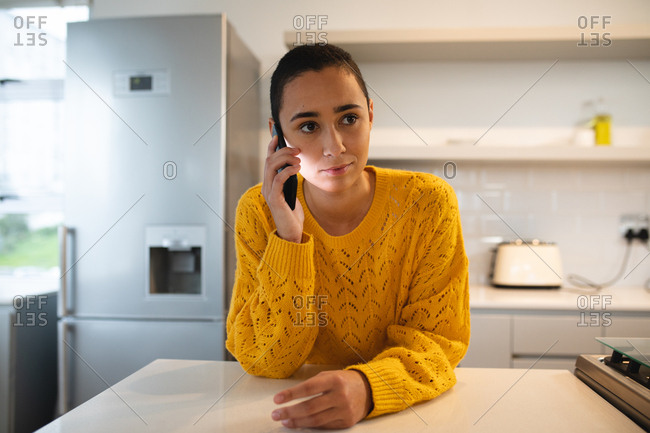 Front view of a mixed race woman with short hair relaxing at home, standing in the kitchen leaning on the worktop, having a phone call on a smartphone