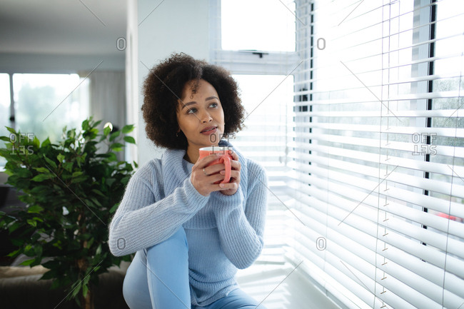 Front view of a mixed race woman relaxing at home, sitting on a window seat looking out of the window, holding a cup of coffee and smiling