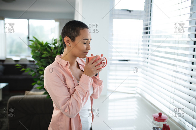 Side view of a mixed race woman with short hair relaxing at home, standing in the living room by a window seat looking out of the window, enjoying a cup of coffee, with eyes closed and smiling