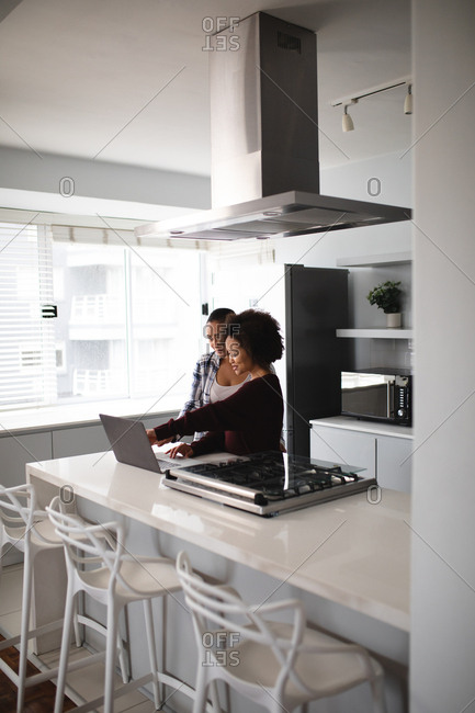 Side view close up of a mixed race female couple relaxing at home, standing in the kitchen using a laptop computer together and smiling
