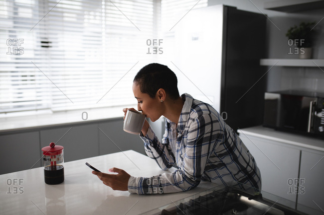 Side view of a mixed race woman with short hair relaxing at home, standing in the kitchen leaning on the worktop, using a smartphone and drinking a cup of coffee