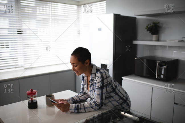Side view of a mixed race woman with short hair relaxing at home, standing in the kitchen leaning on the worktop and using a smartphone, a cup and a pot of coffee beside her