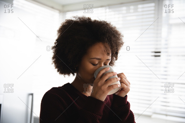 Front view of mixed race woman relaxing at home, enjoying drinking a cup of coffee, holding it with both hands, with her eyes closed