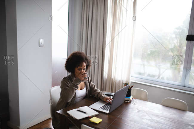 Front view of a mixed race woman sitting at a table at home, drinking a cup of coffee and using a laptop computer