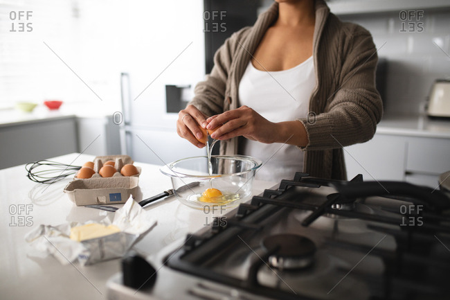 Front view mid section of a mixed race woman at home, standing in the kitchen at a worktop by the hob preparing breakfast, breaking an egg into a bowl