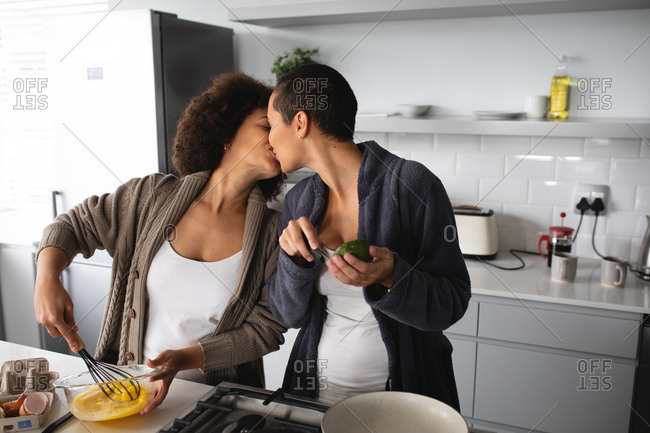 Front view of mixed race female couple relaxing at home, standing in the kitchen kissing while they prepare breakfast together