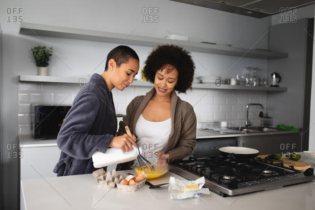 Front view of mixed race female couple relaxing at home, standing in the kitchen preparing breakfast together and smiling, one pouring milk into a bowl while the other mixes it with the eggs