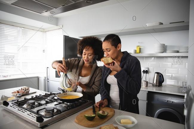 Front view of mixed race female couple relaxing at home, standing in the kitchen making breakfast together, talking and eating