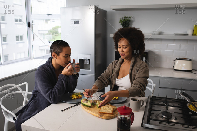 Front view of mixed race female couple relaxing at home, sitting on chairs at the kitchen island eating breakfast and drinking coffee