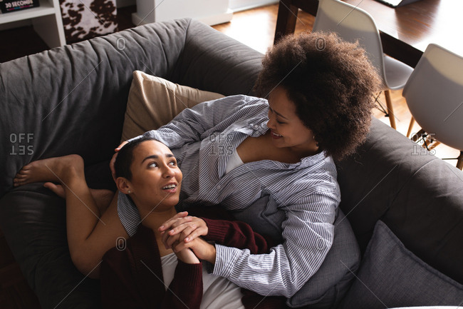 High angle view of a mixed race female couple relaxing at home in the living room on the couch together in the morning, one woman lying with her head on the lap of her partner, holding hands and looking at each other smiling