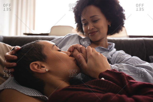 Side view close up of a mixed race female couple relaxing at home in the living room on the couch together in the morning, one woman lying with her head on the lap of her seated partner, holding and kissing her hand