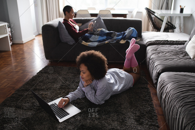 Side view of a mixed race female couple relaxing at home in the living room, one reclining on the couch with a blanket over her legs using a smartphone, the other lying on the floor using a laptop computer