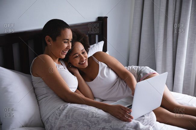 Side view of a mixed race female couple relaxing at home in the bedroom, sitting up in bed using a laptop computer together and smiling