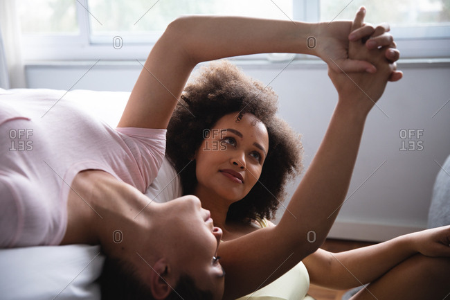 Front view close up of a mixed race female couple relaxing at home in the bedroom in the morning, one lying on her back on the bed and the other sitting beside her on the floor, holding hands and smiling