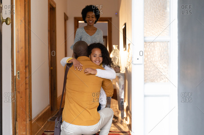 Front view of a young African American girl hugging her father as he kneels in the corridor at home, and smiling over his shoulder, with her mother standing behind her smiling