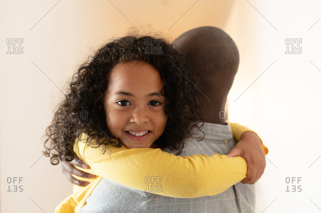 Front view close up of a young African American girl with long curly hair hugging her father as he holds her in the corridor at home, and smiling over his shoulder