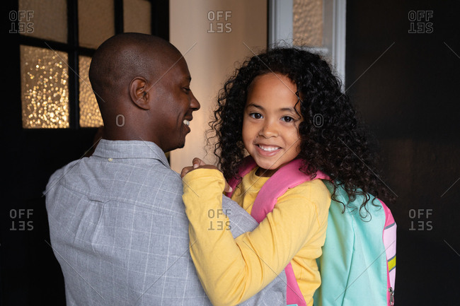 Front view close up of a young African American girl with long curly hair wearing a rucksack, smiling to camera as her father holds her in the corridor at home