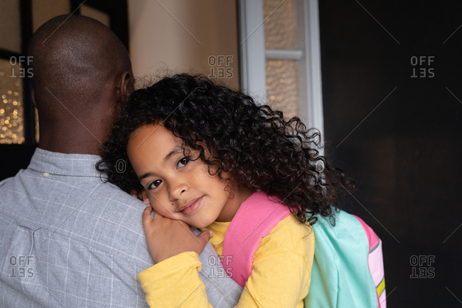 Front view close up of a young African American girl with long curly hair wearing a rucksack, smiling to camera and leaning on the shoulder of her father, as he holds her in the corridor at home