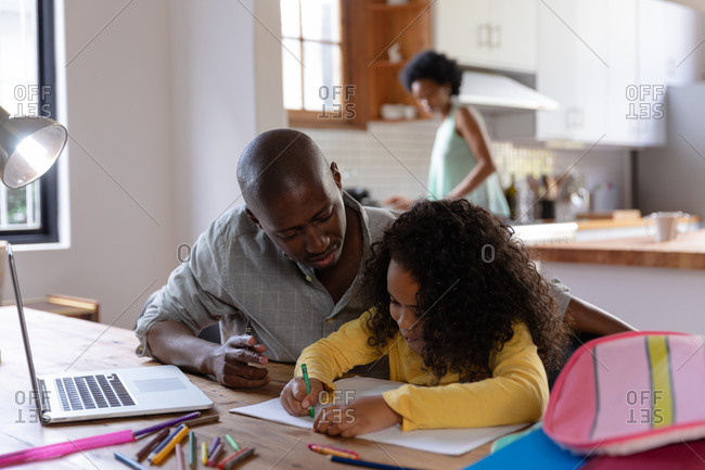 Front view of an African American man at home, sitting at a table with his young daughter watching her drawing in a schoolbook, a laptop computer on the table in front of him, with the mother standing in the kitchen in the background