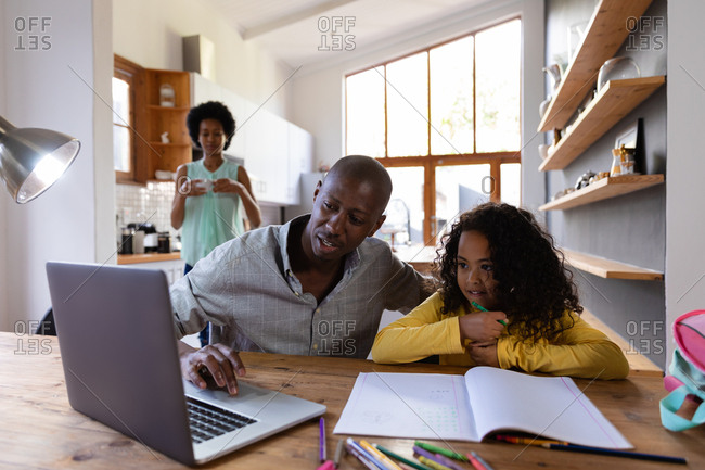 Front view of an African American man at home, sitting at a table with his young daughter looking at a laptop computer together, a schoolbook on the table in front of her, with the mother standing in the kitchen in the background