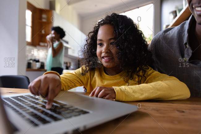 Front view close up of a young African American girl at home, sitting at a table with her father looking at a laptop computer together, the girl pressing the computer keyboard and smiling, with the mother standing in the kitchen in the background