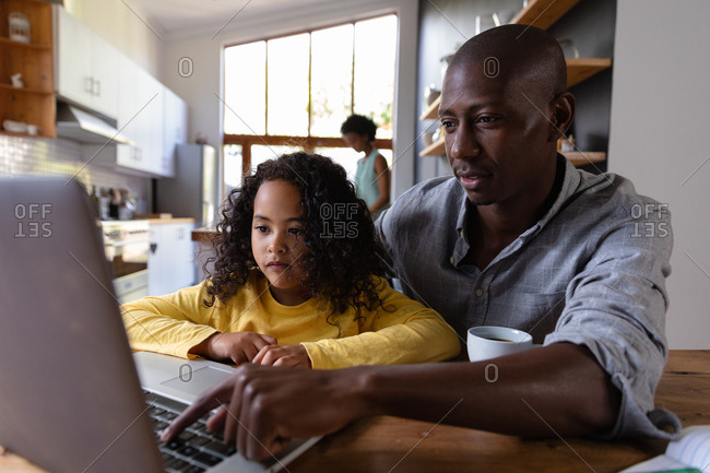 Front view close up of a young African American girl at home, sitting at a table with her father looking at a laptop computer together, the father pressing the computer keyboard and smiling, with the mother standing in the kitchen in the background