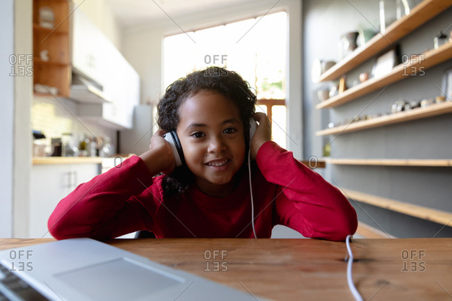 Front view close up of a young African American girl at home, sitting at the dinner table listening with headphones on, plugged into a laptop computer on the table in front of her, looking to camera and smiling