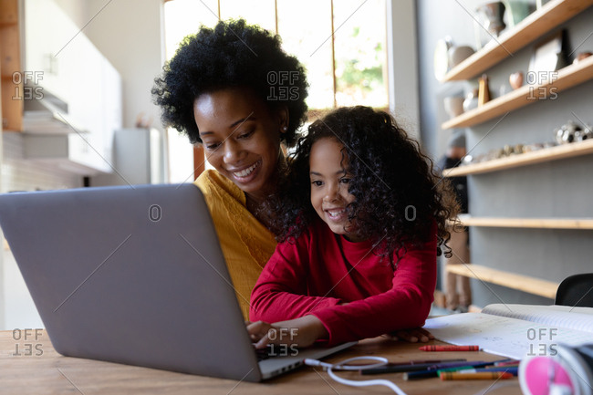 Front view close up of a young African American girl at home, sitting at a table with her mother looking at a laptop computer together, the daughter pressing the computer keyboard and both smiling