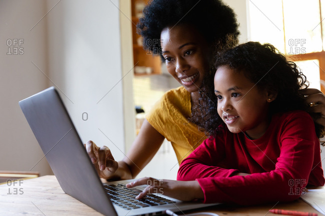 Side view close up of a young African American girl at home, sitting at a table with her mother looking at a laptop computer together, the daughter pressing the computer keyboard and both smiling