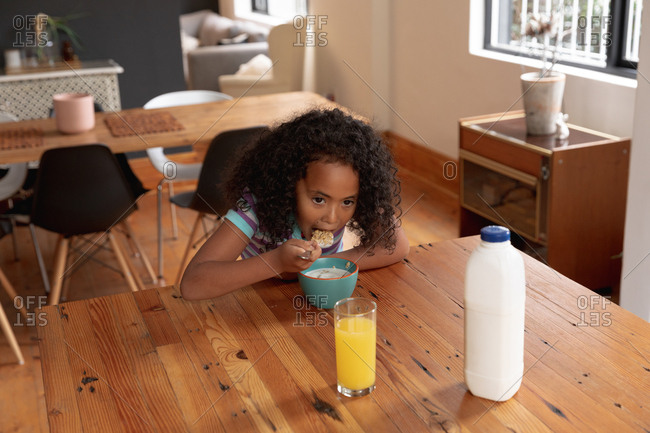 High angle view of a young African American girl at home in the kitchen, sitting at a table eating breakfast cereal, a glass of orange juice and a bottle of milk on the table in front of her