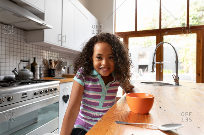 Portrait of a young African American girl at home in the kitchen, sitting at the kitchen island in the morning, with a bowl of breakfast cereal and a spoon in front of her, smiling to camera
