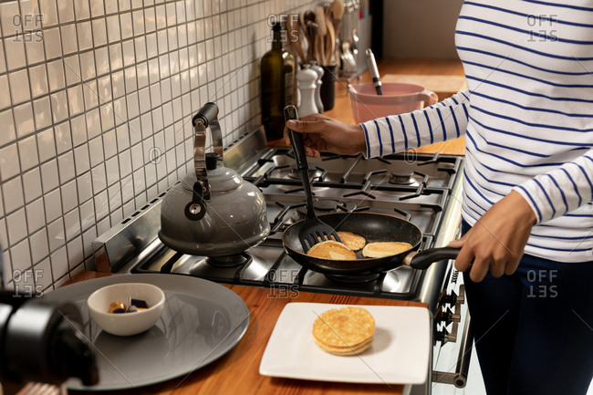 Mid section of an African American woman at home in the kitchen, standing at the hob cooking pancakes in a frying pan