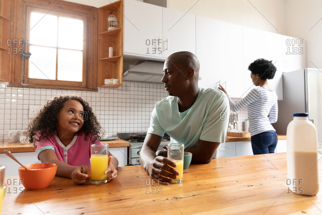 Front view of a young African American girl and her father at home in the kitchen in the morning, sitting at the kitchen island with glasses of orange juice talking and smiling, the mother standing in the background
