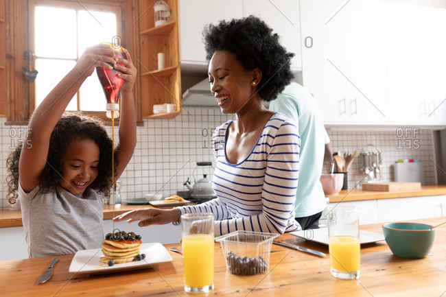 Front view of a young African American girl and her mother at home in the kitchen in the morning, sitting at the kitchen island, the girl pouring sauce on her pancakes and the mother laughing, with the father standing in the background cooking