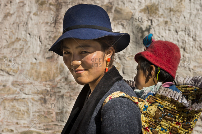 October 1, 2016: Tibet, Drepung Monastery, woman carries child on the back