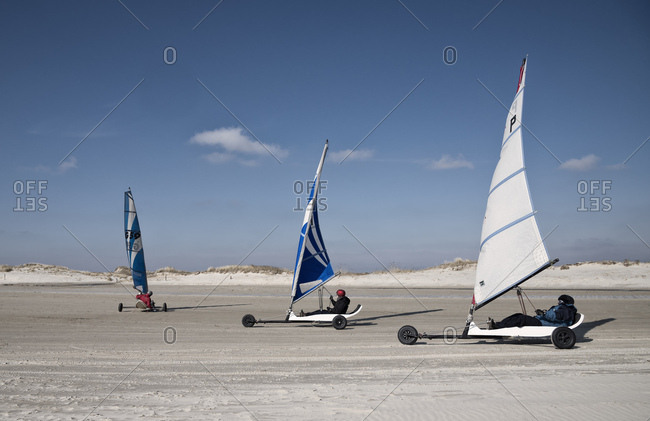 March 27, 2014: three beach sailor on the sandy beach sail with the wind