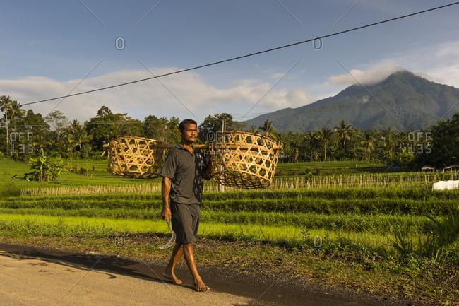 Bali Indonesia -May 27, 2016:  Man carries baskets, in the background the mountain Gunung Batu Karu