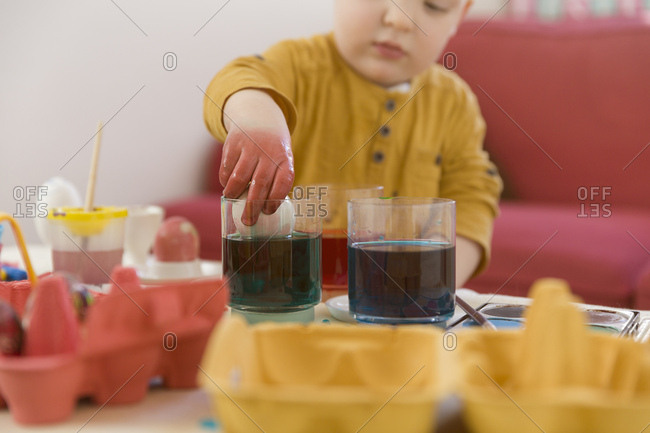 Toddler, dyeing Easter egg, hand in the glass