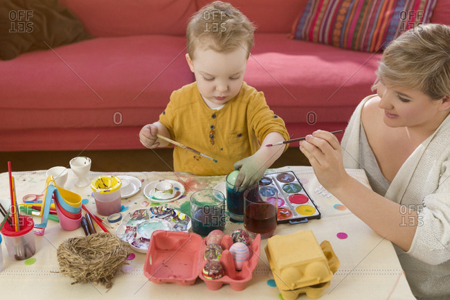 Mother, toddler, dyeing Easter eggs, smeared, colorful hands