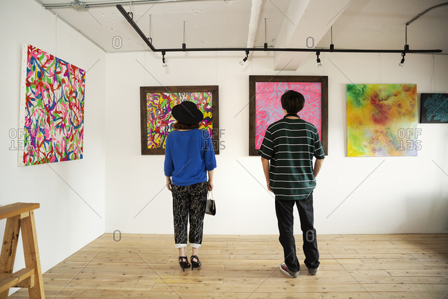 Rear view of Japanese man and woman looking at abstract painting in an art gallery.