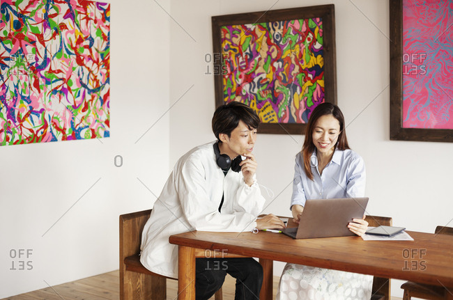 Japanese man and woman siting at a table in an art gallery, looking at laptop computer.